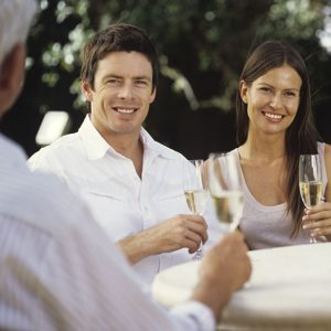 Young couple sitting at table talking to mature couple with champagne